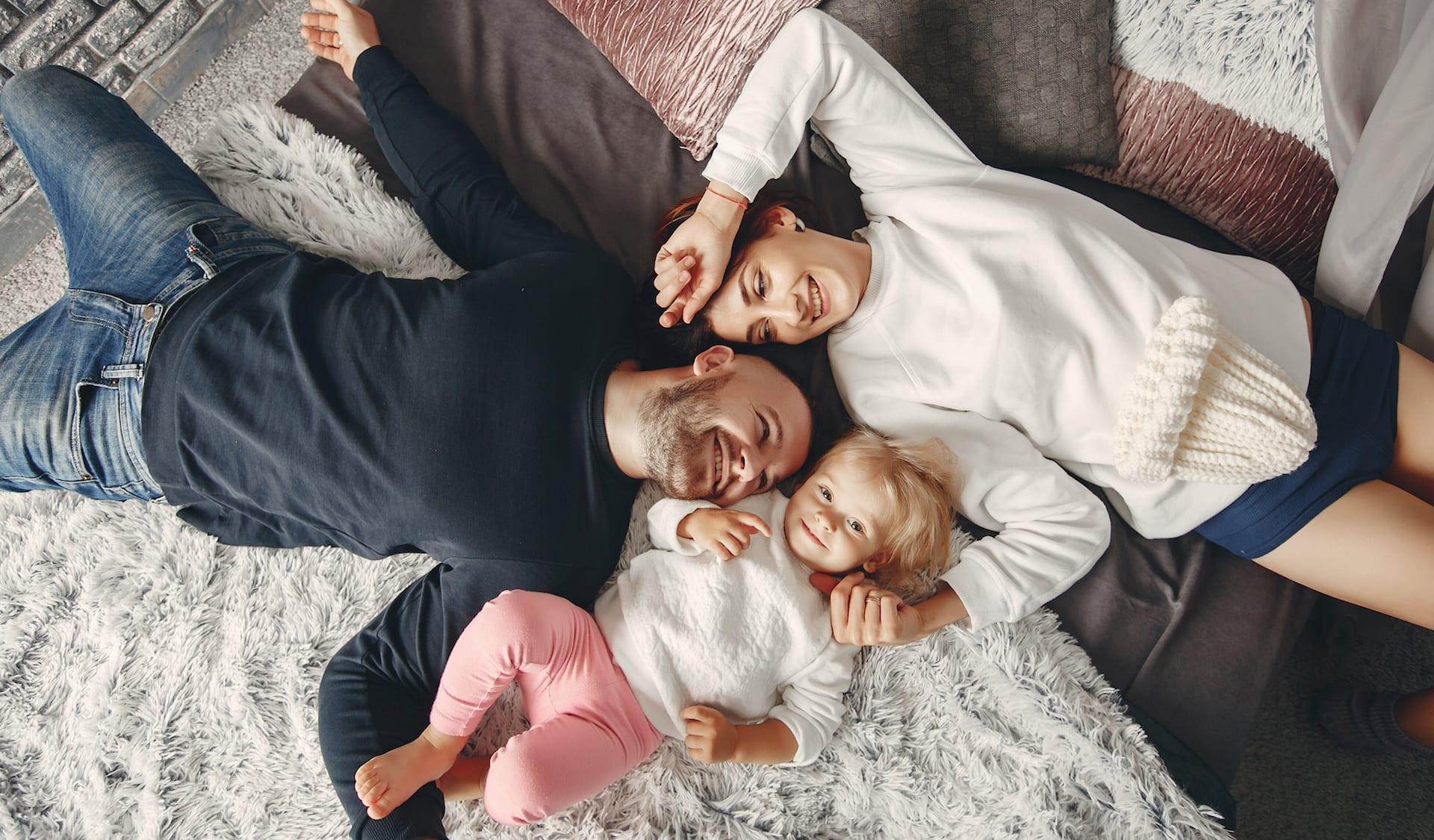 Für Arkitura ist die Familie besonders wichtig. Familie, Mutter Vater und Kind liegen glücklich am Teppich