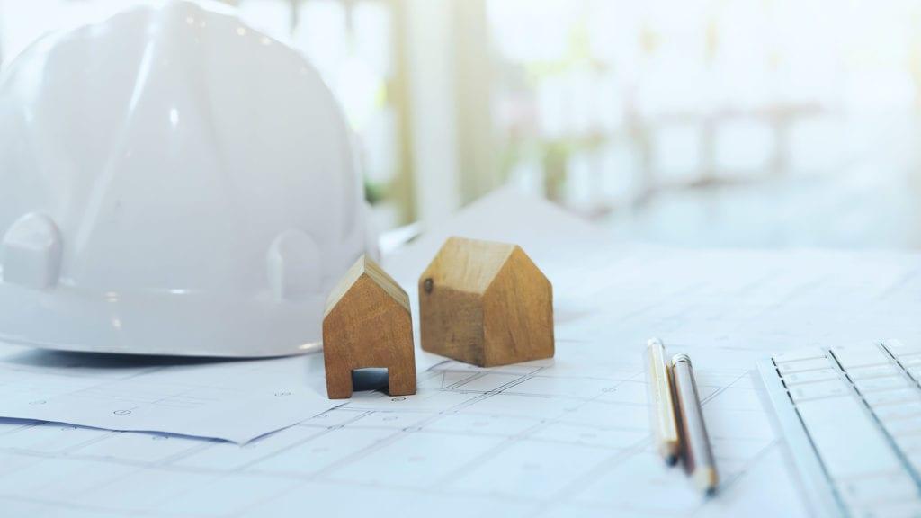 Arkitura setzt auf traditionelle Holzbauweise mit erfahrenen Partnern - kleine Holzhäuser stehen auf einem Plan