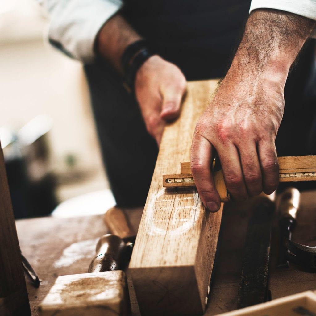 Arkitura setzt auf traditionelle Holzbauweise mit erfahrenen Partnern - Tischler beim Bearbeiten des Holzes